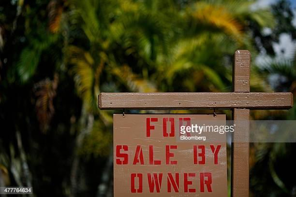 A 'For Sale By Owner' sign stands in front of a house in Fort Lauderdale Florida US on Tuesday June 16 2015 The National Association of Realtors is...
