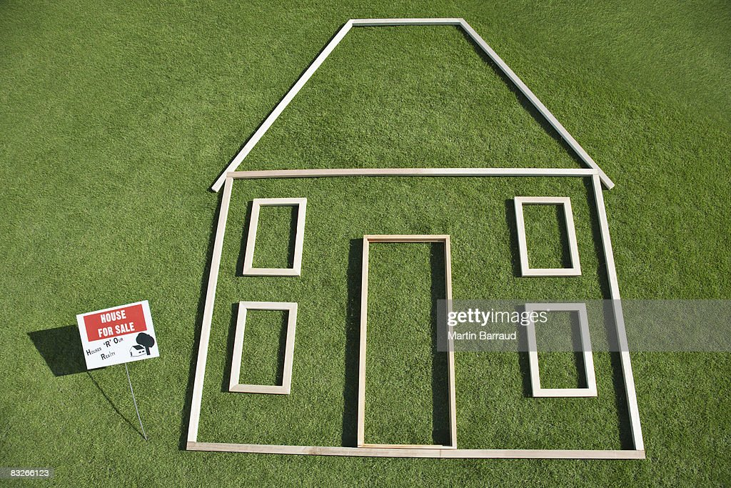 For sale' sign and house outline in grass : Stock Photo