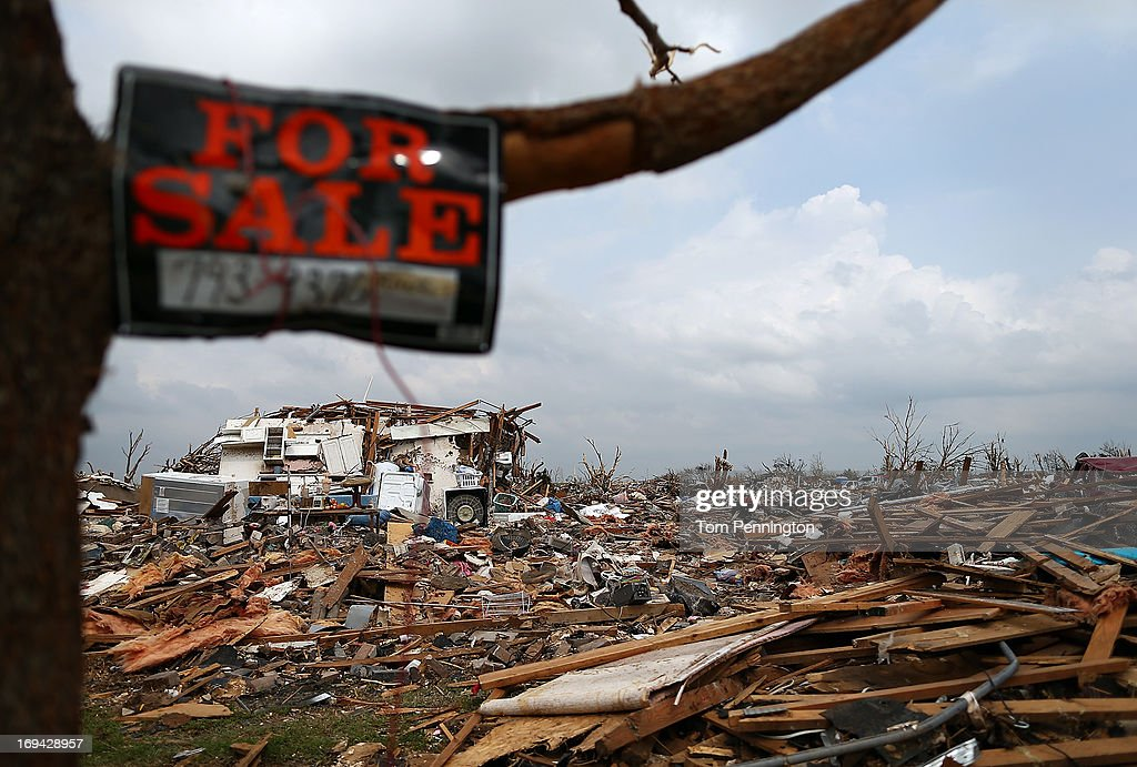 A 'For Sale' sign hangs in a tree in a storm ravaged neighborhood on May 24, 2013 in Moore, Oklahoma. The tornado of EF5 strength and two miles wide touched down May 20 killing at least 24 people and leaving behind extensive damage to homes and businesses. U.S. President Barack Obama promised federal aid to supplement state and local recovery efforts.