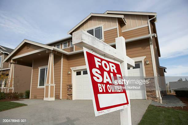 'For Sale' sign in front of house (focus on sign)