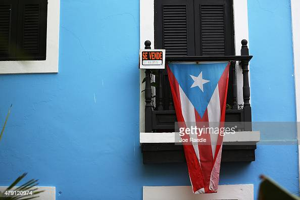 A for sale sign is seen hanging from a balcony next to a Puerto Rican flag in Old San Juan as the island's residents deal with the government's $72...
