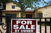 A for sale sign is seen in front of a home on August 21 2015 in Miami Florida According to the National Association of Realtors US home resales rose...