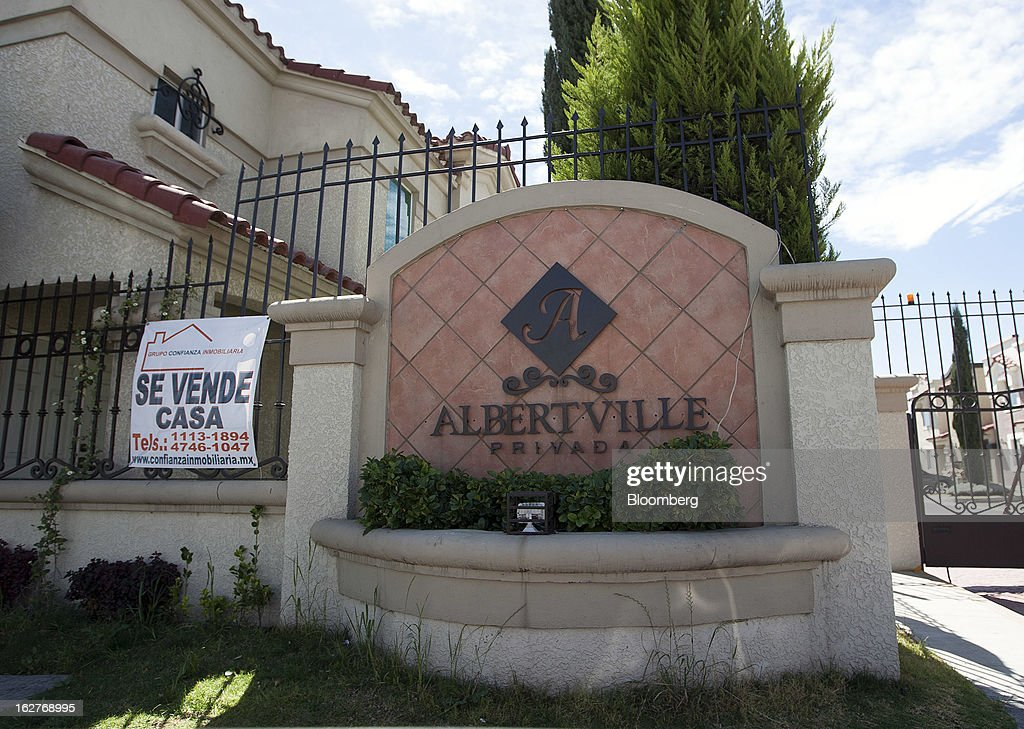 A for sale sign, left, hangs on a gate inside the Urbi Desarrollos Urbanos SAB's Urbi Quinta Montecarlo housing development in Cuautitlan Izcalli, Mexico, on Monday, Feb. 25, 2013. Urbi Desarrollos Urbanos SAB, the Mexican homebuilder that lost three-fourths of its market value in the past year, will report negative free cash flow to equity for the fourth quarter of 2012, according to a company official with direct knowledge of the matter. Photographer: Susana Gonzalez/Bloomberg via Getty Images