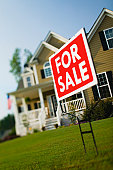 For Sale sign on front lawn of large detached house