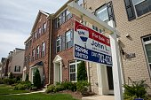 A 'For Sale' sign sits in the front yard of a townhouse June 23 2015 in Northeast Washington DC Purchases of new homes in the US rose in May to the...