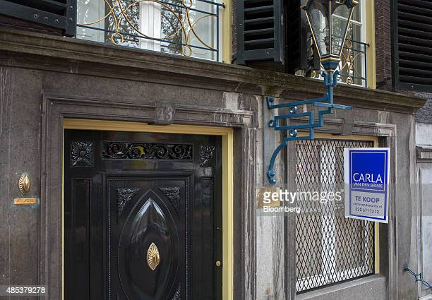 A for sale signs sits on the window grille of residential property in Amsterdam Netherlands on Wednesday Aug 26 2015 Seven years after a global...