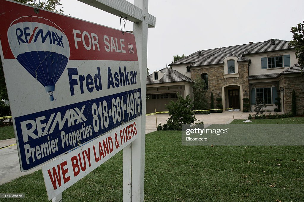 A 'for sale' signs stand outside a home in Arcadia, California, U.S., on Sunday, July 21, 2013. Sales of previously owned houses unexpectedly dropped in June, hurt by a lack of supply and rising mortgage rates that may slow the rebound in the U.S. real-estate market. Photographer: Jonathan Alcorn/Bloomberg via Getty Images