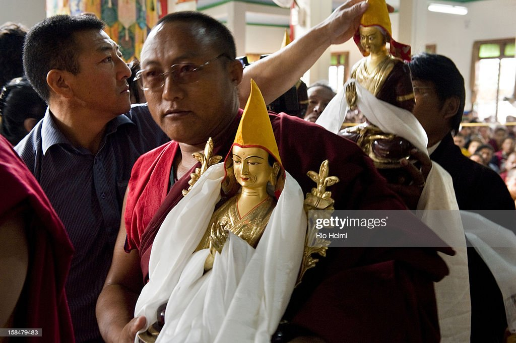 For two weeks 20,000 devotees from around the world attended the Jangchub Lamrim teachings given by His Holiness the Dalai Lama in Mundgod, Karnataka, southern India - here statues are presented to His Hoiness during a long life ceremony at the Drepung temple. One of the Dalai Lama's bodyguards corrects the position of the pandita hat of one of the figures..
