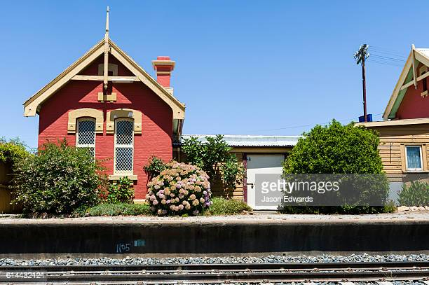An antique railway station and platform in a rural town.