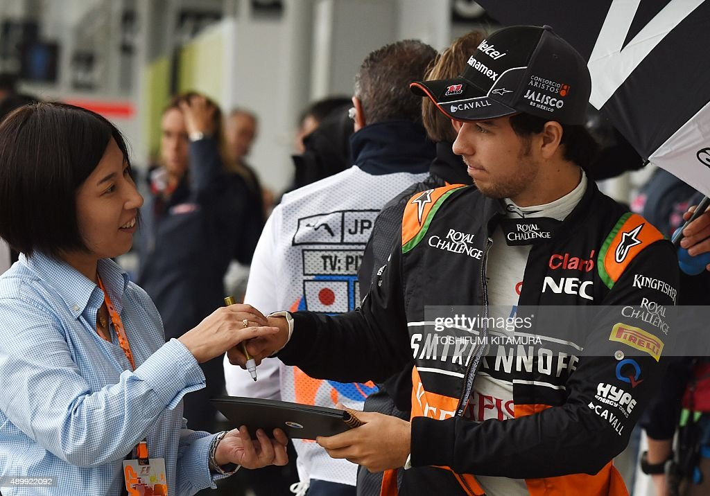Force India driver <a gi-track='captionPersonalityLinkClicked' href=/galleries/search?phrase=Sergio+Perez+-+Mexican+Racing+Driver&family=editorial&specificpeople=7629400 ng-click='$event.stopPropagation()'>Sergio Perez</a> Mendoza of Mexico (R) signs his autograph for a fan prior to the second practice session at the Formula One Japanese Grand Prix in Suzuka on September 25, 2015. AFP PHOTO / TOSHIFUMI KITAMURA