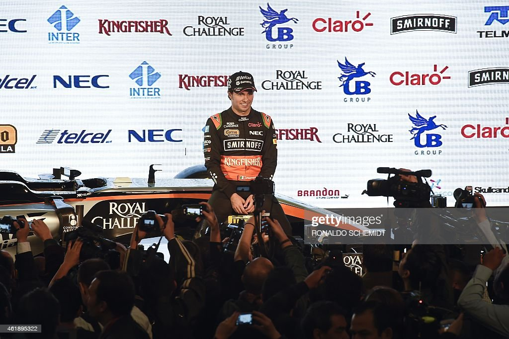Force India drivers Sergio Perez from Mexico poses next to a Force India Formula 1 Team car with the new team livery that will adorn their cars during 2015 FIA Formula One World Championship is presented at the Soumaya Museum in Mexico City, on January 21, 2015.