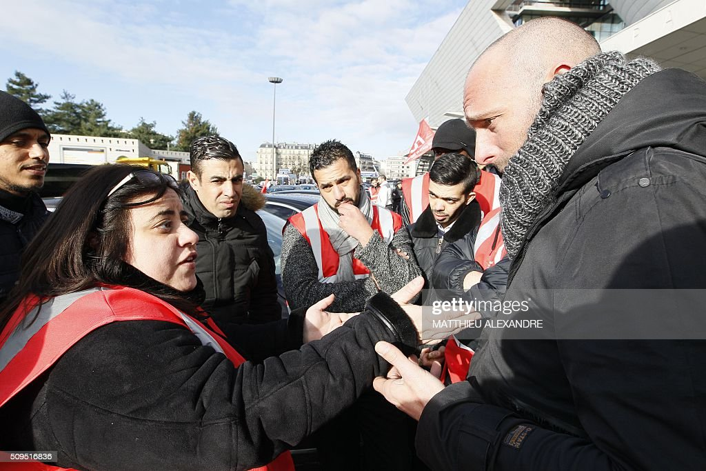 A Force Ouvriere (FO) trade union's representative speaks with a driver as Uber and other ride-hailing companies, known in France as 'voitures de tourisme avec chauffeur' (VTC), a class of companies that allow passengers to book rides with independent professional chauffeurs, gather at Porte Maillot in Paris on February 11, 2016, to defend jobs they believe are threatened by measures the government recently announced in favor of taxis. / AFP / MATTHIEU ALEXANDRE