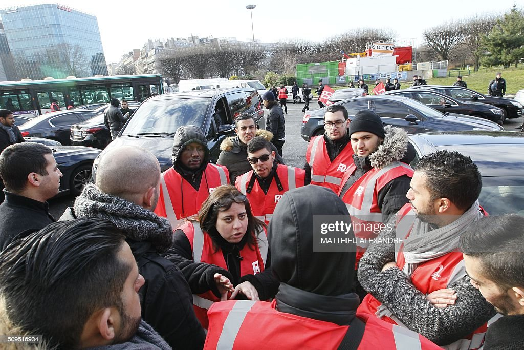 A Force Ouvriere (FO) trade union's representative (C) speaks with a driver as Uber and other ride-hailing companies, known in France as 'voitures de tourisme avec chauffeur' (VTC), a class of companies that allow passengers to book rides with independent professional chauffeurs, gather at Porte Maillot in Paris on February 11, 2016, to defend jobs they believe are threatened by measures the government recently announced in favor of taxis. / AFP / MATTHIEU ALEXANDRE