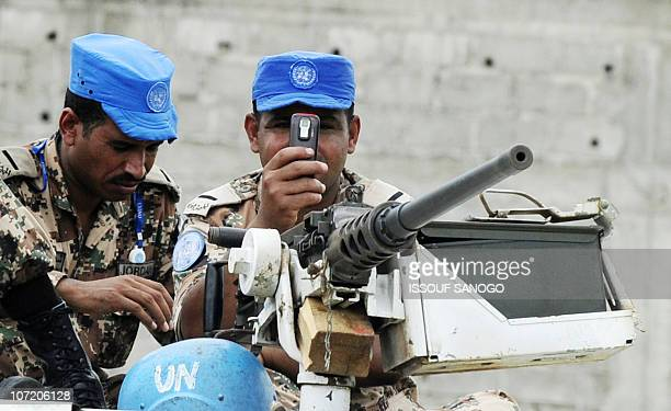 A UN forces soldier takes a picture as they stand guard near a vote counting center on November 29 2010 in Yopougon an Abidjan suburb a day after...