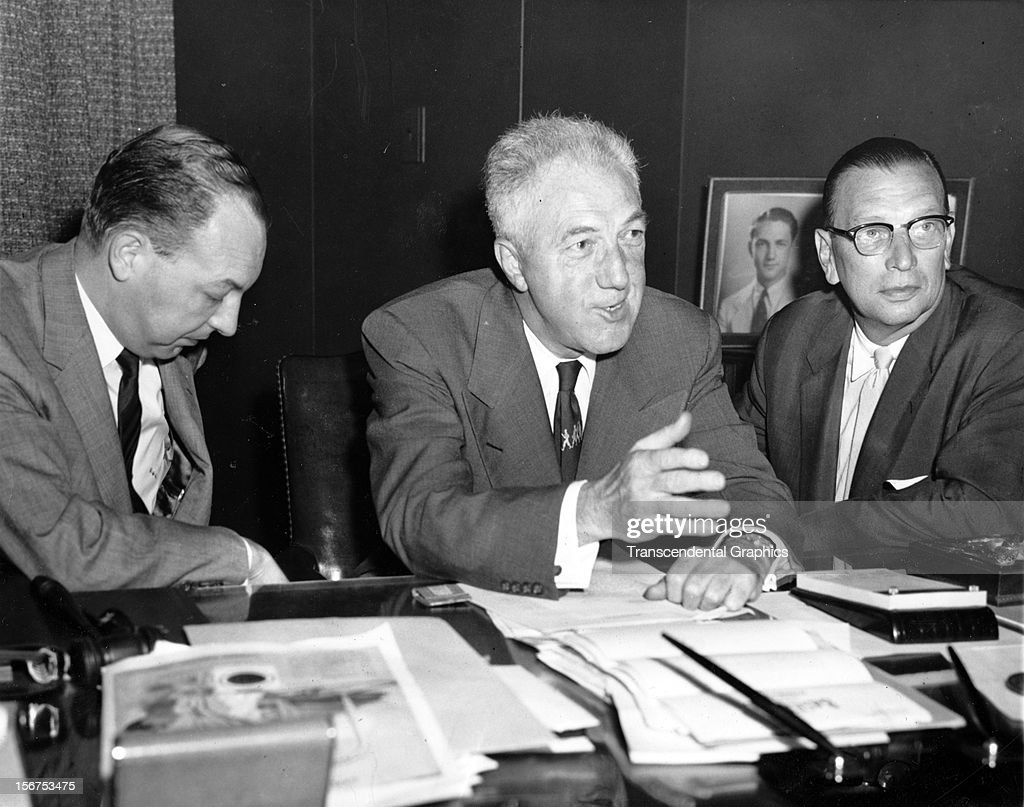 Ford Frick, major league baseball commissioner, center, is interviewed after signing papers with NBC television and Gillette Safety Razor Company for broadcast rights on July 2, 1956 in New York City.