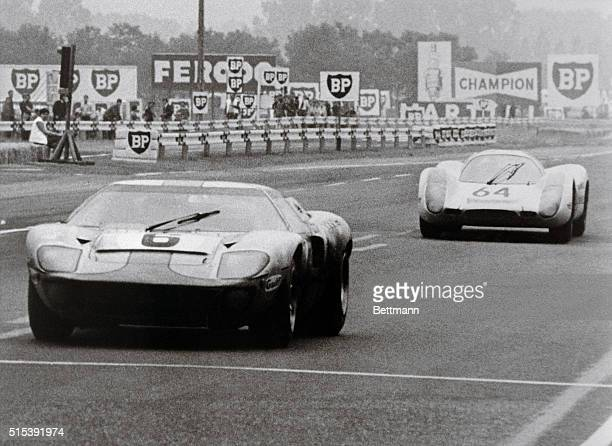 A Ford GT 40 driven by Jackie Ickx of Belgium and Jackie Oliver of Britain flashes across the finish line yards ahead of a German Porsche to win the...