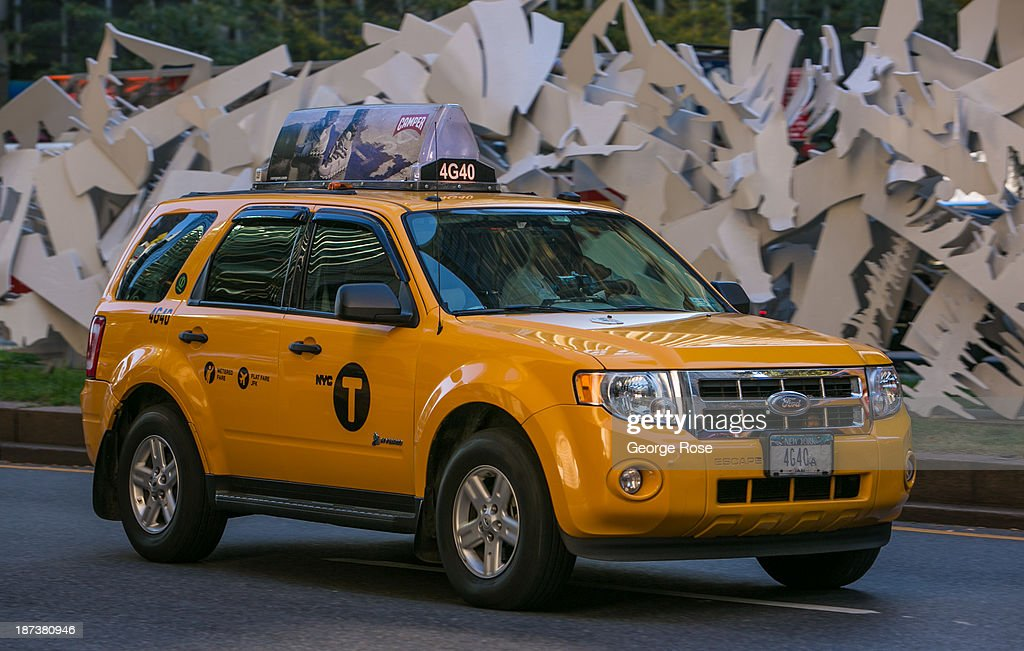 A Ford Hybrid Escape Yellow Taxi races down Park Avenue in midtown on October 21, 2013 in New York City. With a full schedule of conventions and major events taking place throughout Manhattan, millions of global visitors flock to New York City during the fall.