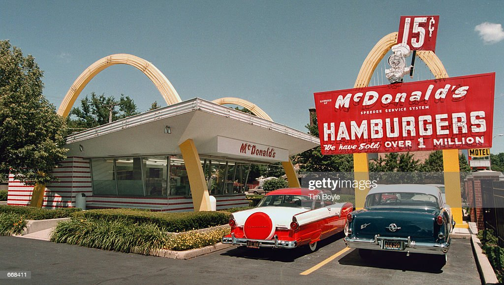 Ford left and a 1955 Oldsmobile are parked in the lot of the McDonald's museum July 14 2000 in Des Plaines IL On this site April 15 1955 Ray Kroc...