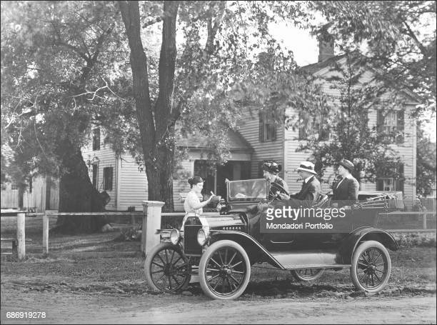A Ford Model T car parked in a dirt road next to the fence of a typical American hoiuse USA 1908