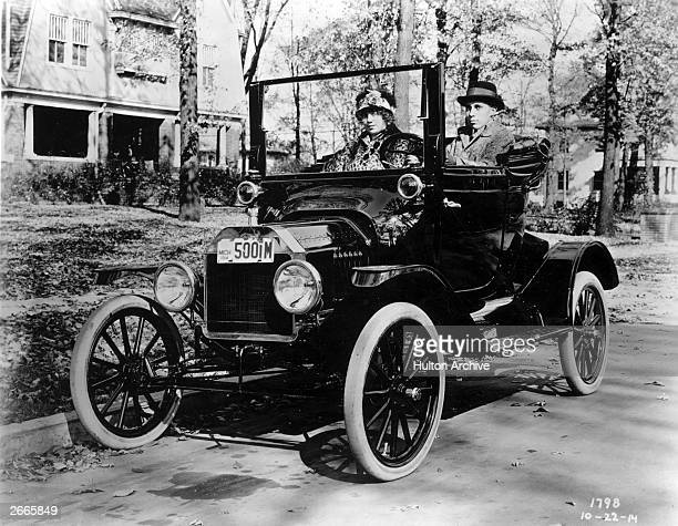 A Ford Model T Couplet convertible car with a couple sitting in it