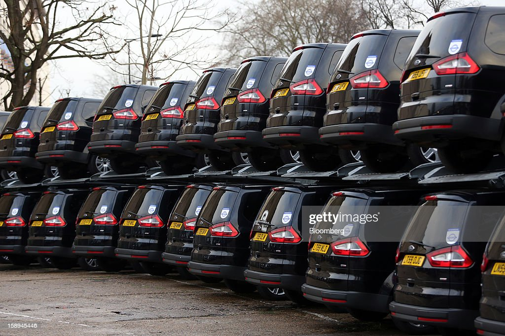 Ford Motor Co. minicabs operated by Addison Lee Plc are stacked on parking ramps on a lot in London, U.K., on Thursday, Jan. 3 2013. U.K. services unexpectedly shrank for the first time in two years in December, clouding the economic outlook as Britain struggles to avoid a triple-dip recession. Photographer: Chris Ratcliffe/Bloomberg via Getty Images