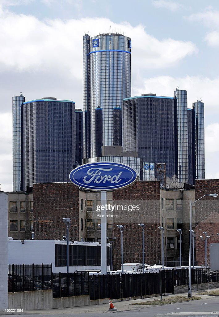 Ford Motor Co. signage is displayed outside of a dealership as the General Motors Co. (GM) headquarters building stands in the distance in Detroit, Michigan, U.S., on Monday, April 1, 2013. U.S. automakers are surging, while Detroit is in such distress that it's being taken over by the state of Michigan today. Photographer: Jeff Kowalsky/Bloomberg via Getty Images