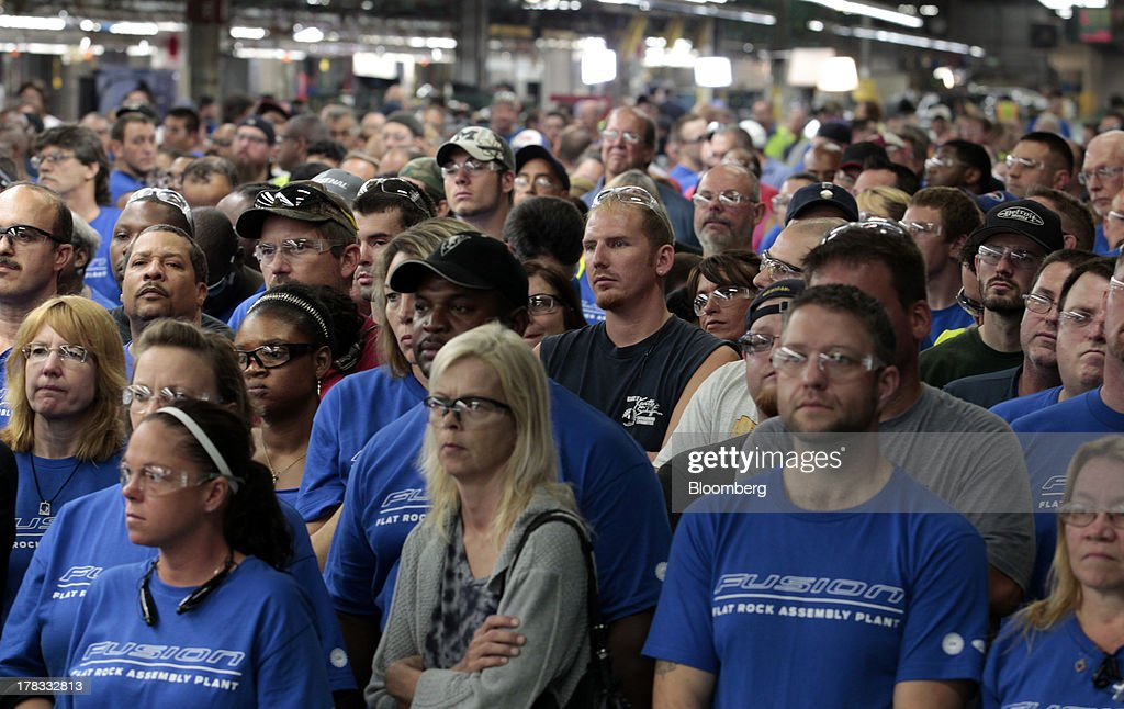 Ford Motor Co. workers watch a ceremony to officially start production of the 2014 Ford Fusion vehicle at the Flat Rock Assembly Plant in Flat Rock, Michigan, U.S., on Thursday, Aug.. 29, 2013. Ford will add a shift of 1,400 new workers at the Flat Rock plant to boost Fusion capacity more than 30 percent, according to a statement from the company. Photographer: Jeff Kowalsky/Bloomberg via Getty Images