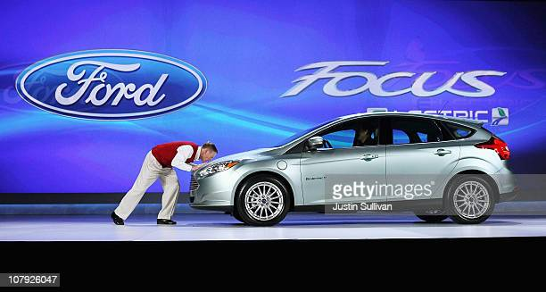 Ford Motor Company President and CEO Alan Mulally kisses the hood of the brand new all electric Ford Focus as he delivers a keynote address at the...
