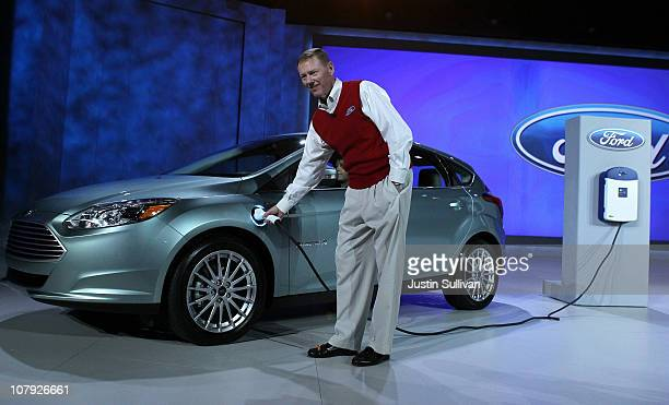 Ford Motor Company President and CEO Alan Mulally plugs in the brand new allelectric Ford Focus after he delivered a keynote address at the 2011...