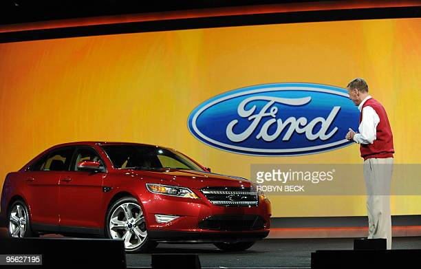 Ford President and CEO Alan Mulally arrives on stage beside a new Ford Taurus to deliver the opening keynote address at the 2010 International...