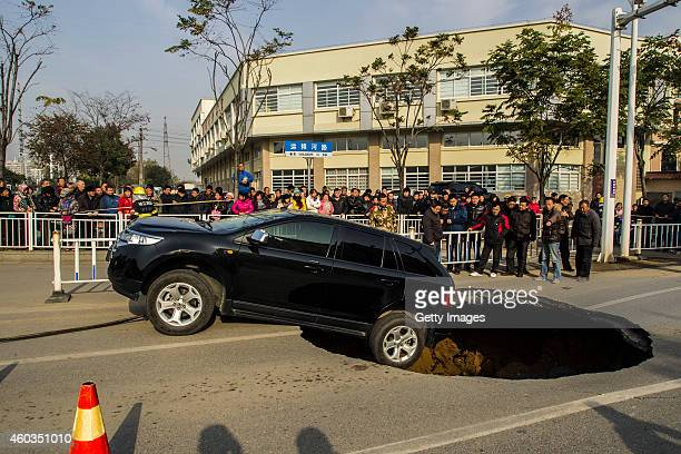 Ford sedan car halts on the verge of a five meters wide and two meters deep hole at Yunlianghe Road on December 12 2014 in Zhenjiang Jiangsu Province...