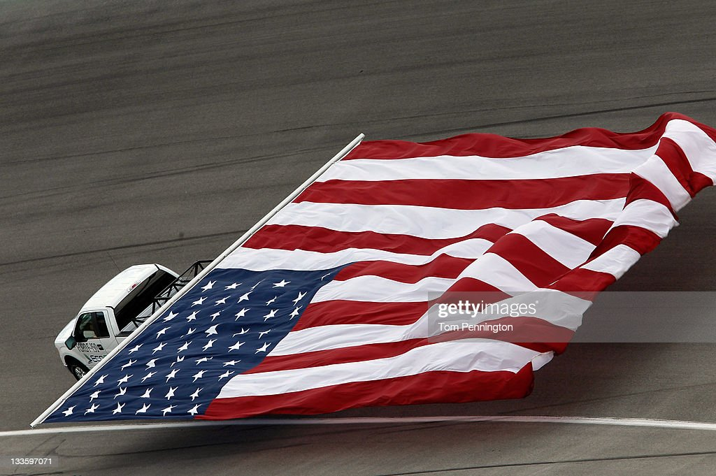 A Ford truck tows an American flag around the track prior to the NASCAR Sprint Cup Series Ford 400 at Homestead-Miami Speedway on November 20, 2011 in Homestead, Florida.