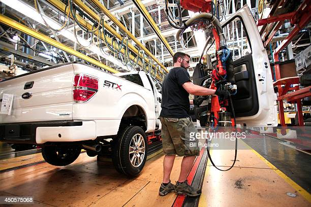 Ford worker Dan Fortune performs a door install on a new 2014 Ford F150 truck on the assembly line at the Ford Dearborn Truck Plant June 13 2014 in...