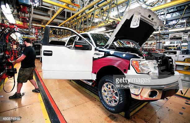 Ford worker Dan Fortune performs a door install on new 2014 Ford F150 truck on the assembly line at the Ford Dearborn Truck Plant June 13 2014 in...