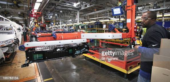 Ford worker loads a battery into a Ford CMAX plugin hybrid vehicle on the assembly line at the Michigan Assembly Plant November 8 2012 in Wayne...