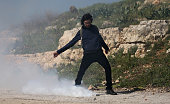 Foreign activist kicks a tear gas canister fired by Israeli soldiers during clashes following a protest against closure of the village road in the...
