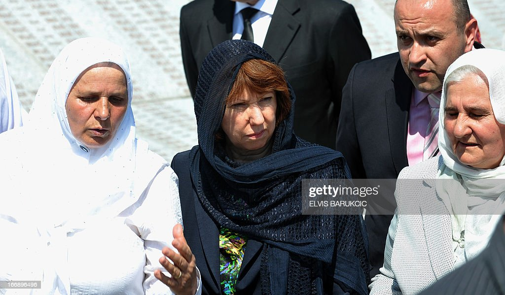 EU Foreign Affairs head Catherine Ashton (C), surrounded by Hatidza Mehmedovic (L) and Munira Subasic (R) of 'Mothers of Srebrenica Association', pays respect to Srebrenica victims at the Memorial Cemetery in Potocari, near Srebrenica, on April 18, 2013. Catherine Ashton arrived in Bosnia early on April 18 and held several meetings with Bosnian top officials and international representatives to the country. In the afternoon Ashton visited Potocari and met with women who survived the 1995 massacre in Srebrenica and lost about 8000 of their most beloved ones. In July 1995, Bosnian Serb forces killed and dumped in mass graves some 8,000 Muslim men and boys, in the worst massacre in Europe since World War II. AFP PHOTO ELVIS BARUKCIC