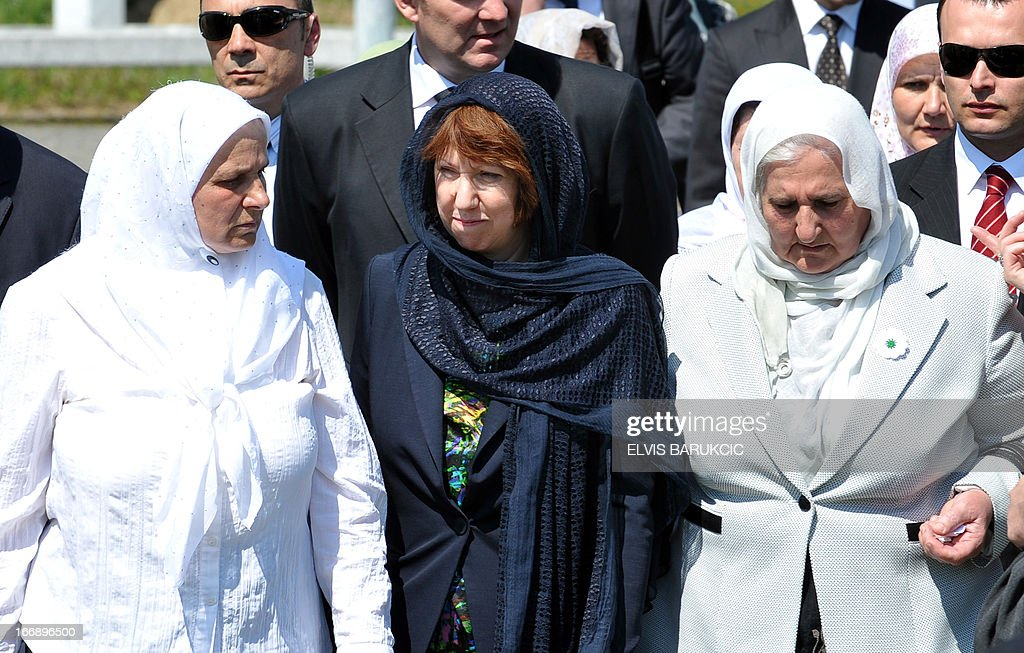EU Foreign Affairs head Catherine Ashton (C), surrounded by Hatidza Mehmedovic (L) and Munira Subasic (R) of 'Mothers of Srebrenica Association', pays respect to Srebrenica victims at the Memorial Cemetery in Potocari, near Srebrenica, on April 18, 2013. Catherine Ashton arrived in Bosnia early on April 18 and held several meetings with Bosnian top officials and international representatives to the country. In the afternoon Ashton visited Potocari and met with women who survived the 1995 massacre in Srebrenica and lost about 8000 of their most beloved ones. In July 1995, Bosnian Serb forces killed and dumped in mass graves some 8,000 Muslim men and boys, in the worst massacre in Europe since World War II.