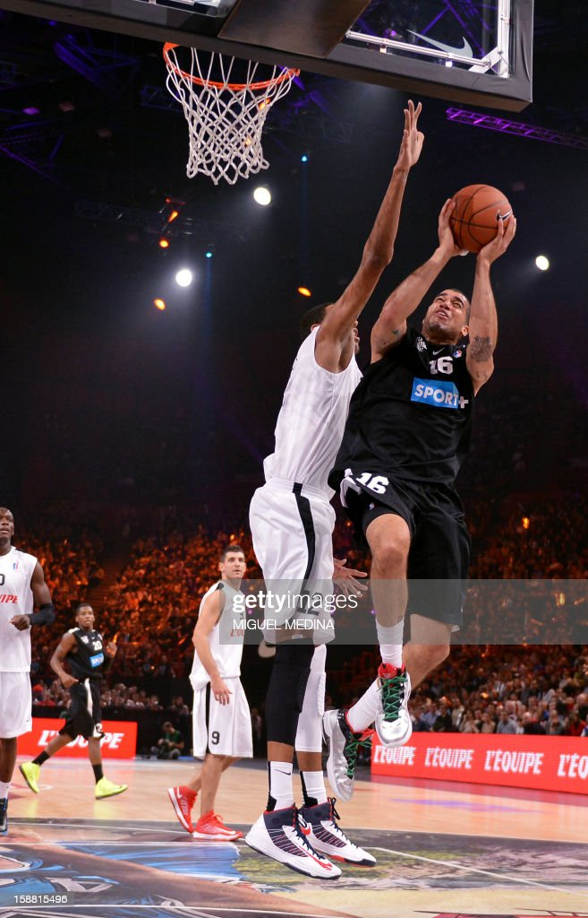 Foreign All Star player, US Blake Schilb (R), vies with French All star player Alexis Ajinca (C) during the France's national basketball league (LNB) 2012 All Star Game on December 30, 2012 at the Palais Omnisport de Paris-Bercy (POPB) in Paris.
