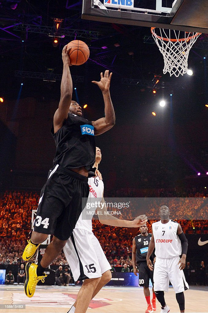 Foreign All Star US player Ahmad Nivins jumps to score against French All star players during the France's national basketball league (LNB) 2012 All Star Game on December 30, 2012 at the Palais Omnisport de Paris-Bercy (POPB) in Paris. AFP PHOTO MIGUEL MEDINA