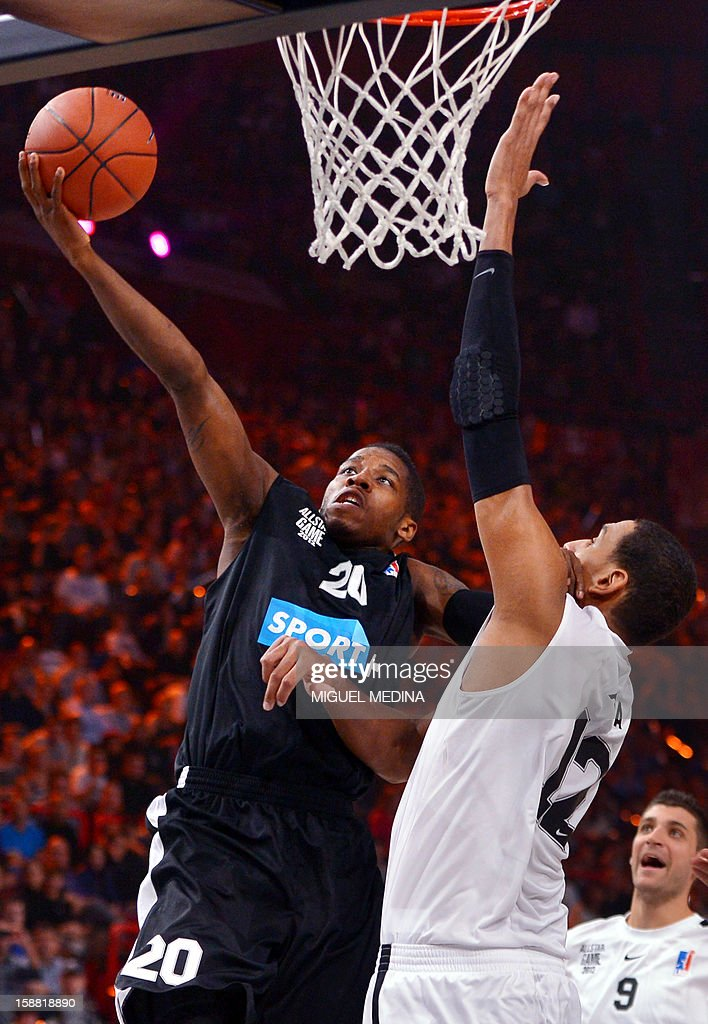 Foreign All Star US player Dwight Buycks (L) vies with French All star player Alexis Ajinca (R) during the France's national basketball league (LNB) 2012 All Star Game on December 30, 2012 at the Palais Omnisport de Paris-Bercy (POPB) in Paris. AFP PHOTO MIGUEL MEDINA