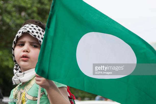 A foreign child seen at the demonstration as she holds one of a Malaysian Islamic political party flag Almost 1000 people gathered outside the United...
