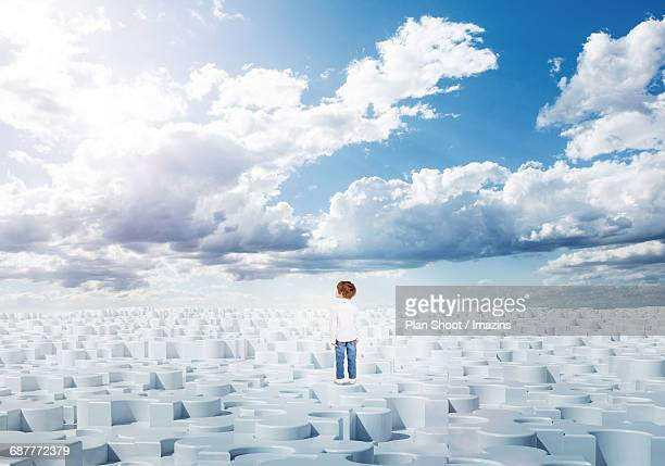 A foreign child standing on a sky and a puzzle shaped ground