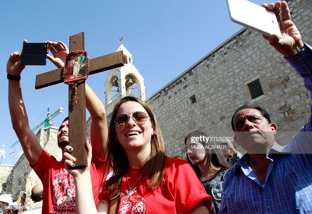 Foreign Christian Orthodox worshippers hold a cross outside the Church of the Nativity in the biblical west bank town of Bethlehem on April 30, 2016, during the Orthodox Easter ceremony of the 'Holy Fire'. The ceremony is marked by the appearance of 'sacred fire' in the two cavities on either side of the Holy Sepulchre, in the Church of the Sepulchre in Jerusalem, and Christians all over the world light candles representing this 'Holy Fire'. The Holy Sepulchre in Jerusalem is the site of the tomb of Jesus Christ according to Christian tradition. / AFP / MUSA