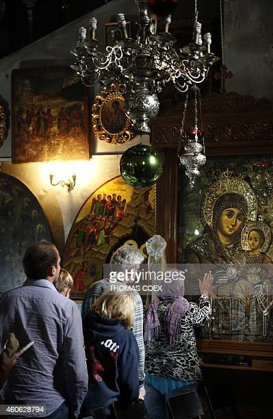 Foreign Christian worshipers pray in front of icons at the Church of the Nativity revered as the site of Jesus Christ's birth in the West Bank town...