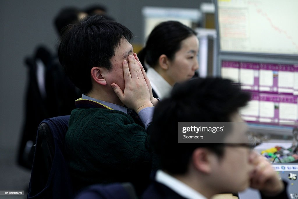A foreign currency dealer covers his face with his hands in a dealing room at the Korea Exchange Bank headquarters in Seoul, South Korea, on Tuesday, Feb. 12, 2013. North Korea conducted its third underground nuclear test today, underscoring a disregard for an international community that has already isolated the totalitarian state from the global economy. Photographer: SeongJoon Cho/Bloomberg via Getty Images