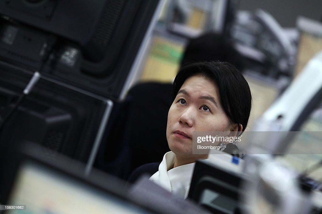 A foreign currency dealer looks at a computer screen in a dealing room at the Korea Exchange Bank headquarters in Seoul, South Korea, on Wednesday, Dec. 12, 2012. South Korea's won traded near a 15-month high and stocks extended gains after North Korea launched a rocket in defiance of international sanctions. Photographer: SeongJoon Cho/Bloomberg via Getty Images