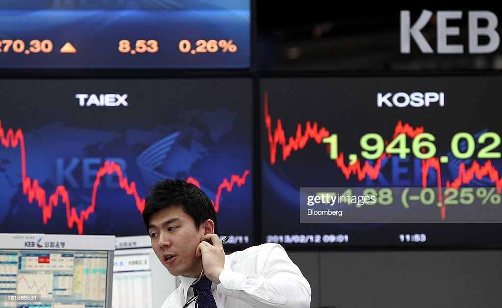 A foreign currency dealer makes a phone call in front of a monitor displaying the Korea Composite Stock Price Index (Kospi), right, in a dealing room at the Korea Exchange Bank headquarters in Seoul, South Korea, on Tuesday, Feb. 12, 2013. North Korea conducted its third underground nuclear test today, underscoring a disregard for an international community that has already isolated the totalitarian state from the global economy. Photographer: SeongJoon Cho/Bloomberg via Getty Images