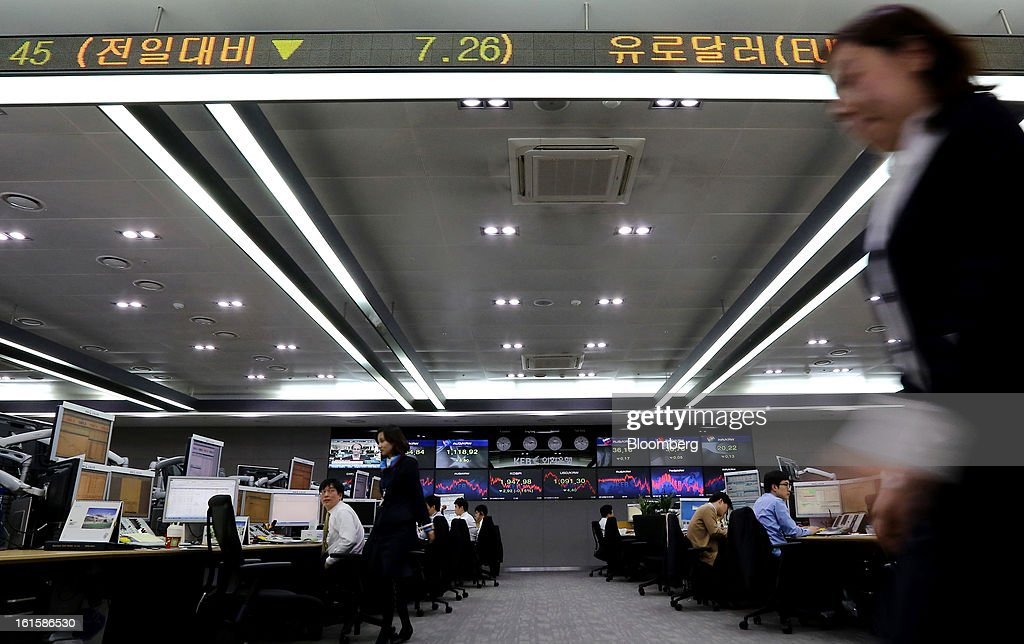 A foreign currency dealer walks past a monitor displaying the Korea Composite Stock Price Index (Kospi) in a dealing room at the Korea Exchange Bank headquarters in Seoul, South Korea, on Tuesday, Feb. 12, 2013. North Korea conducted its third underground nuclear test today, underscoring a disregard for an international community that has already isolated the totalitarian state from the global economy. Photographer: SeongJoon Cho/Bloomberg via Getty Images