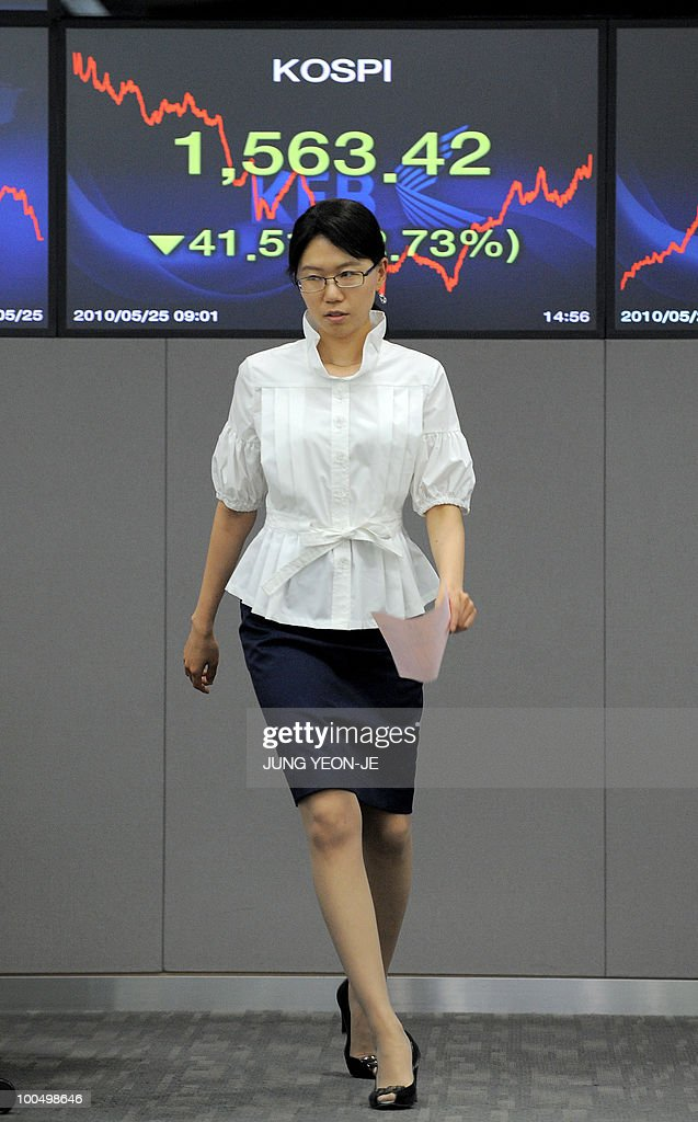 A foreign currency dealer walks past a screen showing South Korea's benchmark stock index at the Korean Exchange Bank in Seoul on May 25, 2010. South Korea's currency and stock markets fell sharply amid escalating tensions over the deadly sinking of a warship and Europe's debt crisis.
